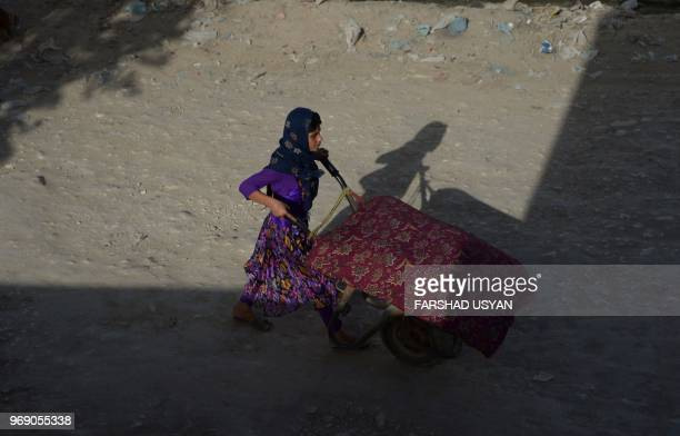 In this photograph taken on June 6 an Afghan girl pushes a wheelbarrow along the road in MazariSharif