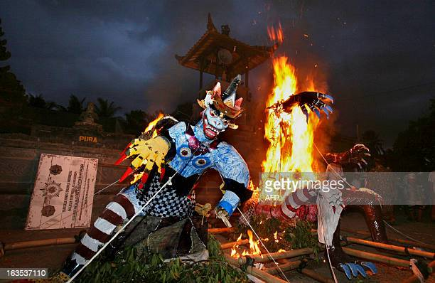 In this photograph taken on March 11 Indonesia's minority Hindu devotees torch an Ogoh Ogoh effigy at a temple courtyard following a religious...