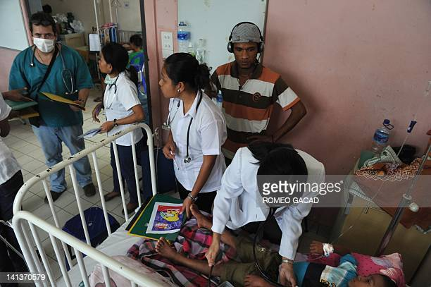 In this photograph taken on March 14 a Cuban doctor guides East Timorese medical interns while a Filipino doctor attends to five year old Josualdo...