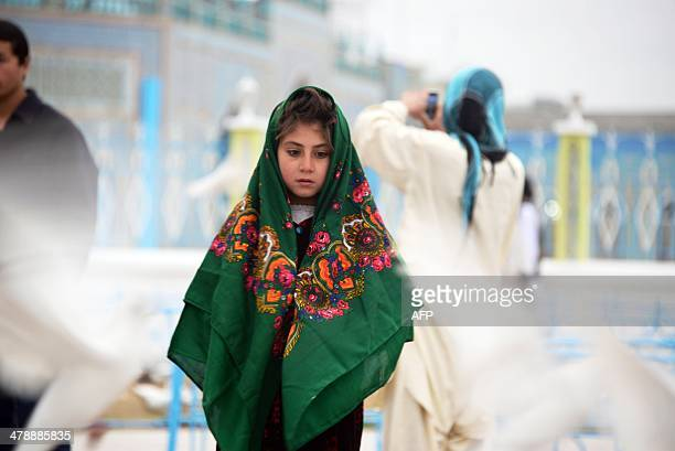 In this photograph taken on March 14 an Afghan child watches the doves in front of the famous Hazrate Ali shrine or 'Blue Mosque' in the northern...