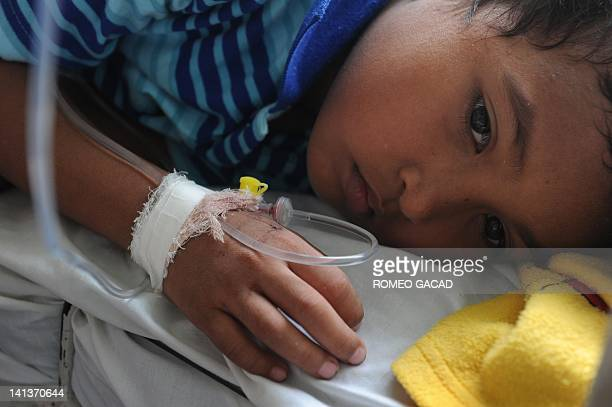 In this photograph taken on March 14 eight year old East Timorese boy Abel Loky recovers from dengue at Dili's National Hospital during a recent...