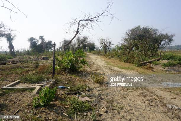 In this photograph taken on March 18 2018 during a Myanmar government arranged press tour charred debris of houses and vegetation are seen in the...