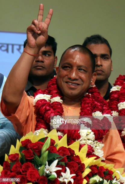 In this photograph taken on March 18 new Chief Minister of the northern Indian state of Uttar Pradesh Yogi Adityanath gestures to supporters as he is...