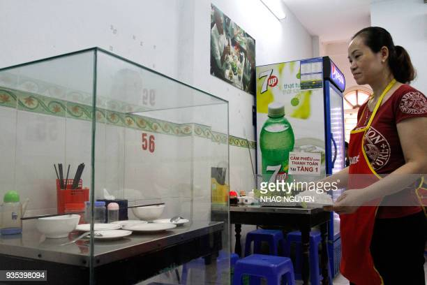 In this photograph taken on March 20 a waitress carries dishes to customers next to the glassencased table where former US President Barack Obama sat...