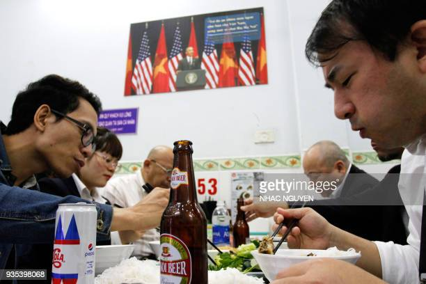 In this photograph taken on March 20 customers enjoy a meal at Bun Cha Huong Lien restaurant now dubbed 'bun cha Obama' with a photograph of former...
