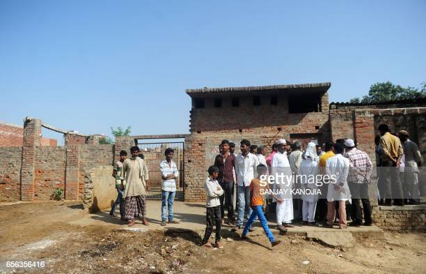 In this photograph taken on March 21 Indian Muslim butchers and traders with family members gather outside a closed illegal slaughter house at Naini...