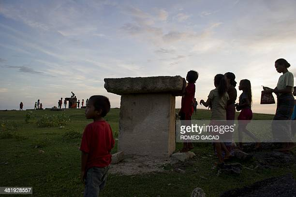 In this photograph taken on March 21 Sumbanese tribeswomen and children give offerings of betel nut during a procession around the tombs in...