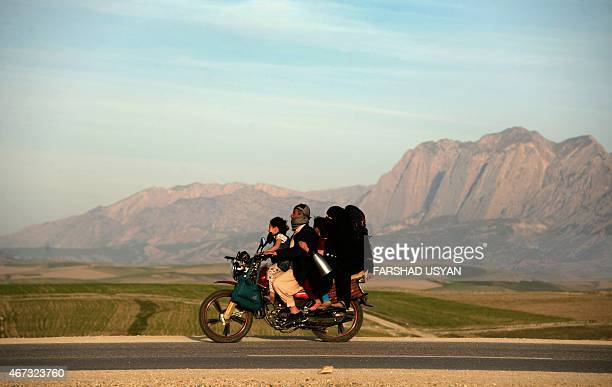 In this photograph taken on March 22 an Afghan family travel on a motorcycle as they travel to celebrate Nowruz which marks the Afghan New Year on...