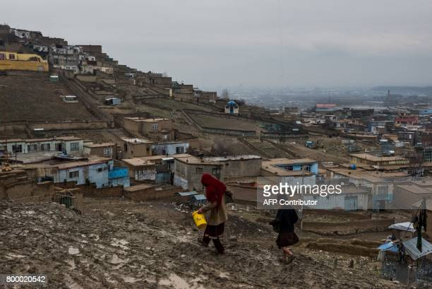 In this photograph taken on March 22 an Afghan resident caries water through the Zanabad 'Widows Hill' on the outskirts of Kabul The first ones...