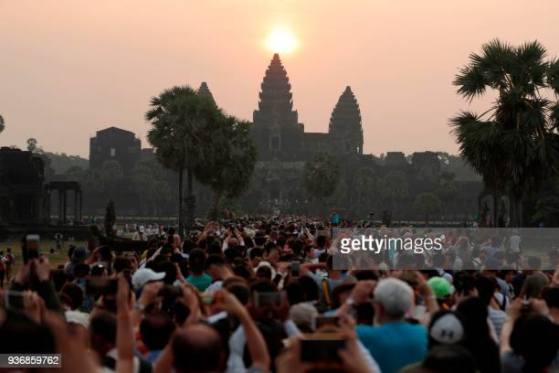 TOPSHOT In this photograph taken on March 22 the sun rises over the central stupa of Angkor Wat temple in Siem Reap The well preserved remains of the...
