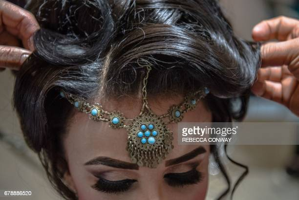 In this photograph taken on March 23 Afghan beauticians affix jewellery to the hairstyle of a bride ahead of her wedding party at a beauty parlour in...