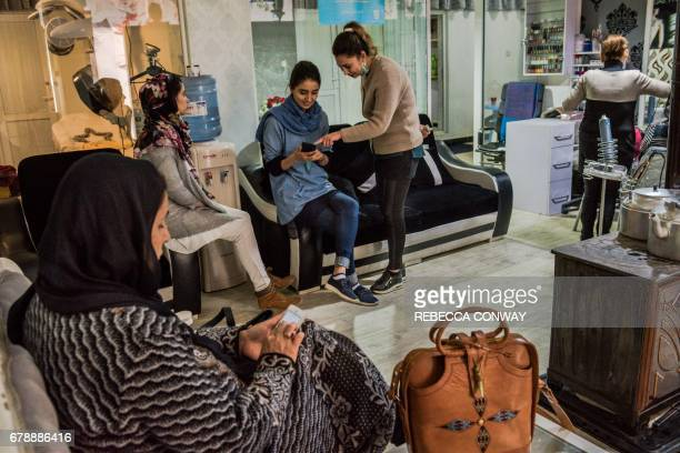 In this photograph taken on March 23 Afghan clients talk in the waiting area of a beauty parlour in Kabul languorous kohlrimmed eyes and bright bold...