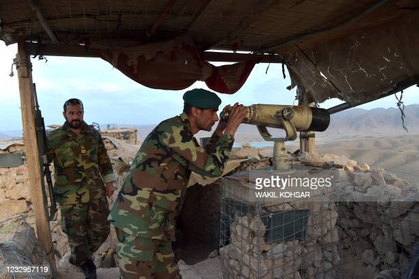 In this photograph taken on March 23 Afghan National Army commander Dost Nazar Andarabi keeps watch with binoculars at an outpost set up against...