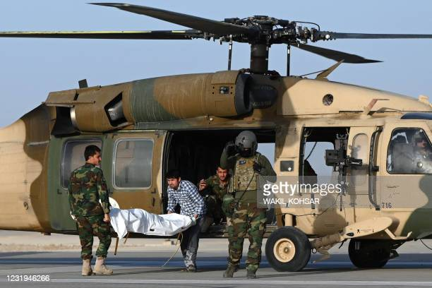 In this photograph taken on March 25, 2021 Afghan National Army soldiers take the dead body of a soldier on a stretcher out from an Afghan Air Force...