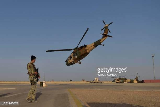 In this photograph taken on March 25, 2021 an Afghan Commandos soldier stands guard as an Afghan Air Force Black Hawk helicopter takes off at the...
