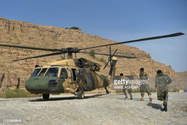 In this photograph taken on March 25 Afghan National Army soldiers unload food items and petrol oil from an Afghan Air Force Black Hawk helicopter at...
