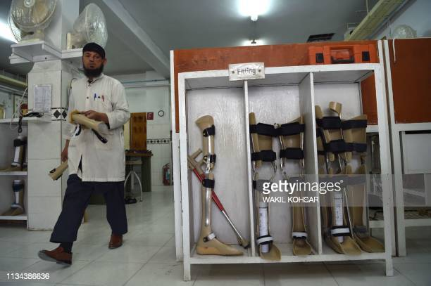 In this photograph taken on March 27 an Afghan orthopaedic technician walks past artificial limbs in a workshop at the International Committee of the...