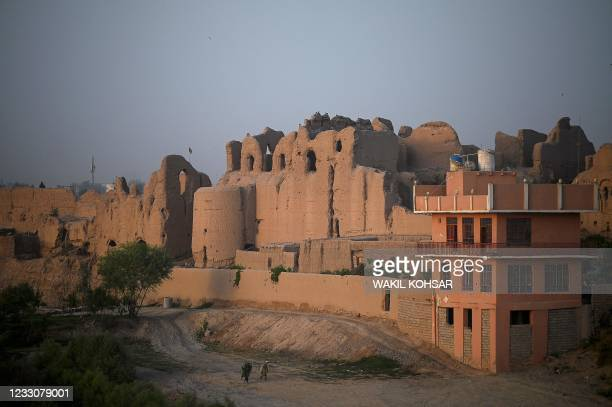 In this photograph taken on March 27 men walk along a pathway near an old palace where internally displaced families live, at the Qal-e-Kohna, a...