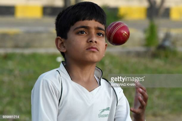 In this photograph taken on March 27 Pakistani child Eli Mikal Khan tosses a ball during a cricket bowling practice at his father's academy in Quetta...