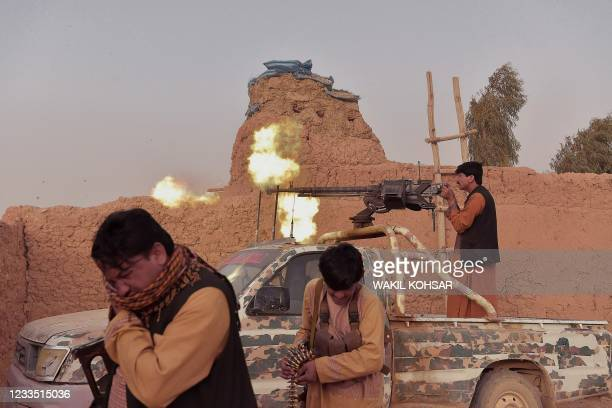 """In this photograph taken on March 28 a member of the anti-Taliban """"Sangorians"""" militia fires a heavy machine gun during an ongoing fight with Taliban..."""