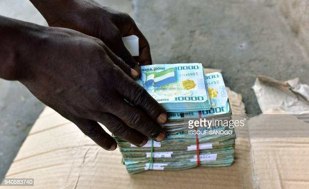 In this photograph taken on March 30 a money changer arranges a bundle of Sierra Leone's currency notes on a pavement in Freetown Despite government...