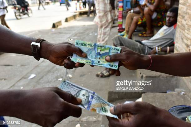 In this photograph taken on March 30 a money changer exchanges a bundle of Sierra Leone currency notes for a 100 US dollar note on a pavement in...