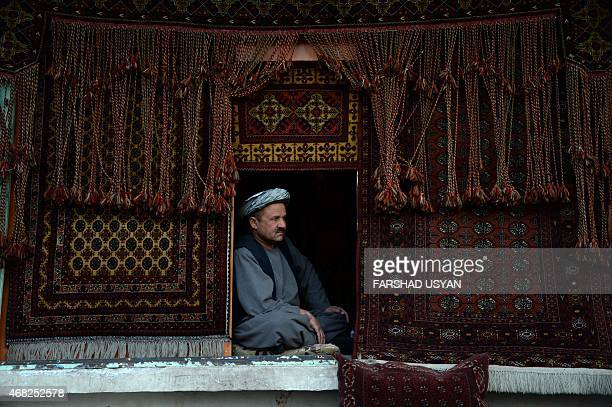 In this photograph taken on March 31 Afghan shopkeeper Saifuddin seats in his carpet shop as he waits for customers at the courtyard of HazrateAli...