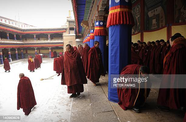 In this photograph taken on March 8 Tibetan Buddhist monks leave their prayer hall after prayers at Taersi Monestry in China's northwest Qinghai...