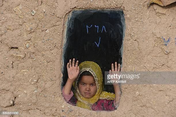 In this photograph taken on May 10 2016 an Afghan girl looks from a window of her home on the outskirts of Herat / AFP / AREF KARIMI