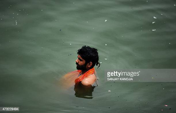 In this photograph taken on May 10 an Indian Sadhu takes a holy dip at Dashasamedh Ghat on the River Ganges in VaranasiAFP PHOTO/SANJAY KANOJIA