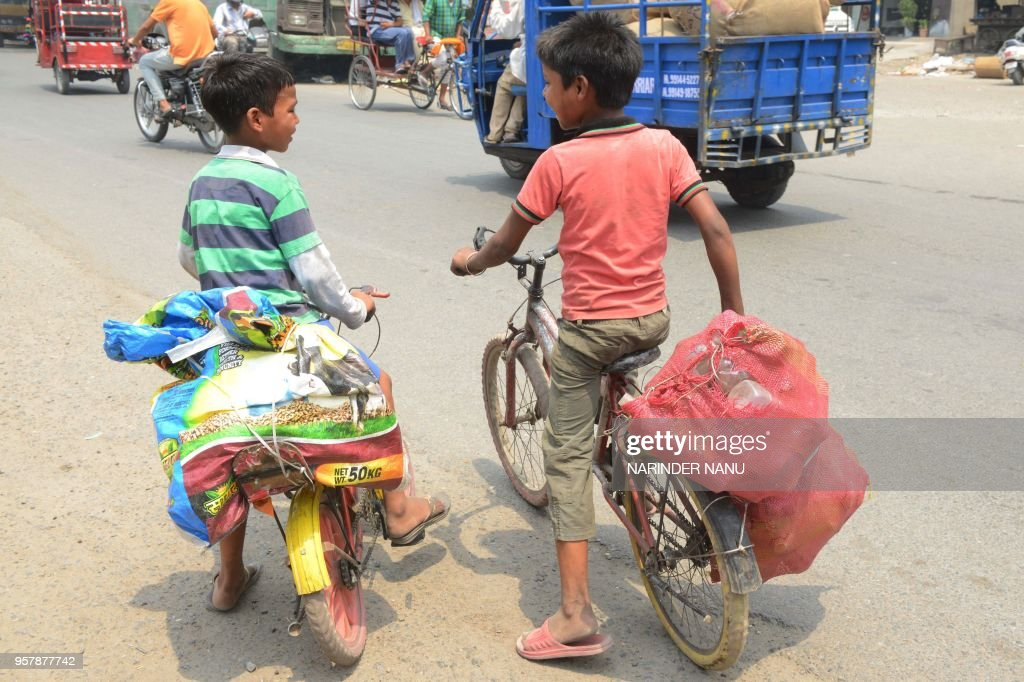In this photograph taken on May 12 Indian children carry empty plastic bottles in sacks on their bicycles in Amritsar