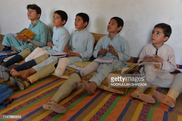 In this photograph taken on May 14 Afghan disabled children, belonging to Hamisha Gul family who lost their legs following unexploded rocket...