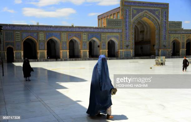 In this photograph taken on May 17 2018 an Afghan burqa clad woman walks in a mosque during holy month of Ramadan in Herat Muslims throughout the...