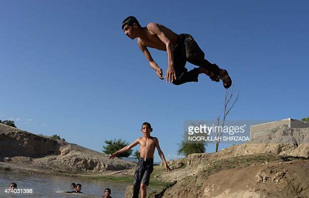 In this photograph taken on May 19 an Afghan youth dives into a ditch of muddy water to beat the heat on the outskirts of Jalalabad in Nangarhar...