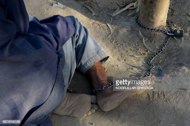 In this photograph taken on May 2 a mentally ill Afghan patient is chained at the Mia Ali Baba holy shrine in the village of Samar Khel on the...