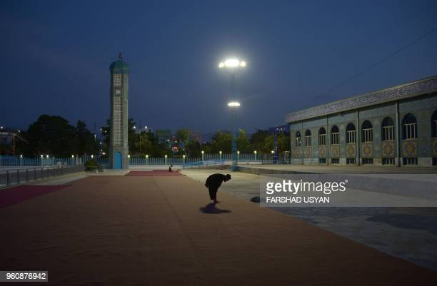 In this photograph taken on May 20 an Afghan Muslim man offers his evening pray during the Islamic holy month of Ramadan in the courtyard of the...