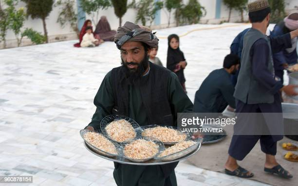 In this photograph taken on May 20 an Afghan resident distributes foods as others wait to break their fast during the holy month of Ramadan in...