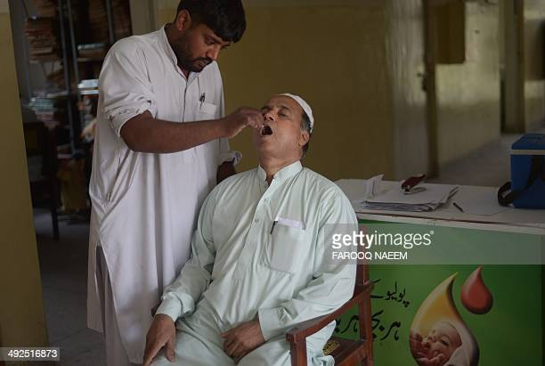 In this photograph taken on May 20 Pakistani resident Muhammad Sharif Malik receives polio vaccination drops from a health worker before travelling...