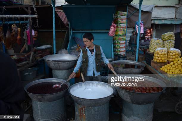 In this photograph taken on May 21 An Afghan boy sells homemade snacks from his stall during the Islamic holy month of Ramadan in MazariiSharif...