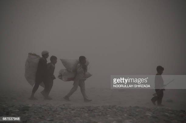 TOPSHOT In this photograph taken on May 23 Afghan children carry bags as they walk through dense fog on the outskirts of Jalalabad / AFP PHOTO /...
