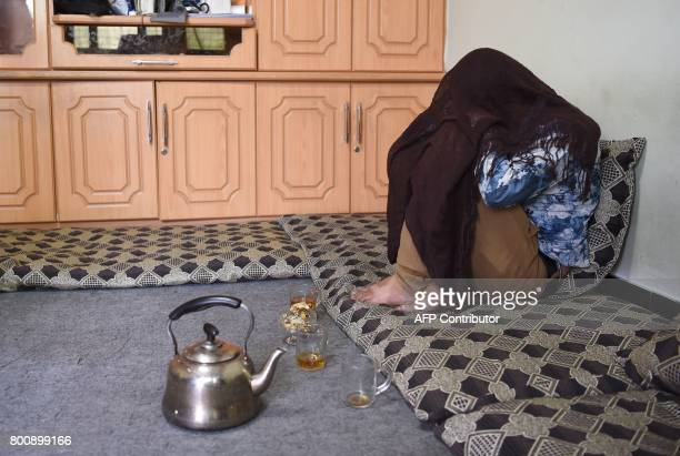 In this photograph taken on May 23 Afghan former bacha Jawed, now 19 and working as a dancing boy, sits with his face covered during an interview...