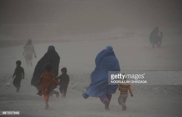 In this photograph taken on May 23 Afghan women with their children walk through dense fog on the outskirts of Jalalabad / AFP PHOTO / NOORULLAH...