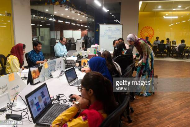 In this photograph taken on May 24 people work at their desks at the National Incubation Centre , a start-up incubator, in Lahore. - Pakistan's...