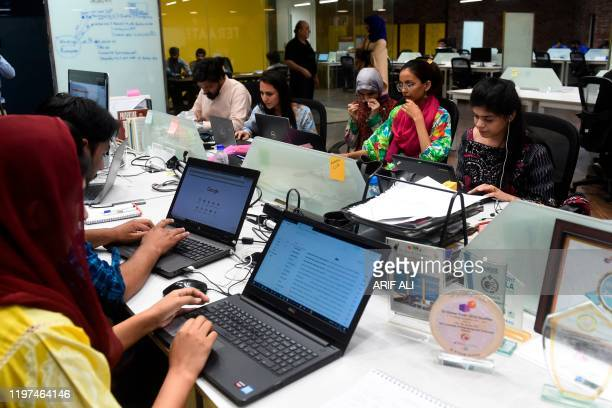 In this photograph taken on May 24 People work at their stations at the National Incubation Centre , a start-up incubator, in Lahore. - Pakistan's...