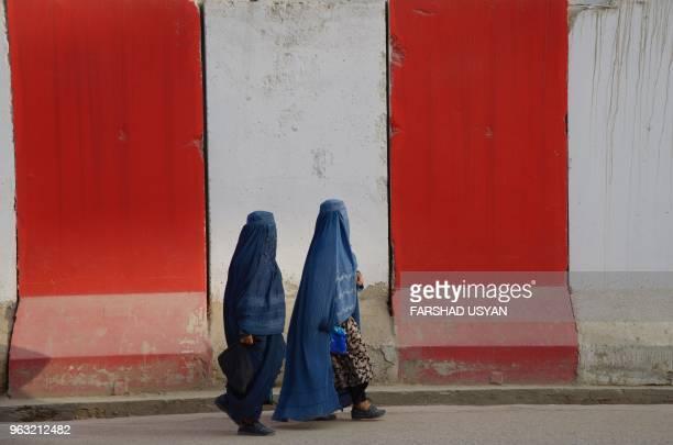 TOPSHOT In this photograph taken on May 27 2018 Afghan clad burqa women walk past blast walls along the roadside in MazariSharif