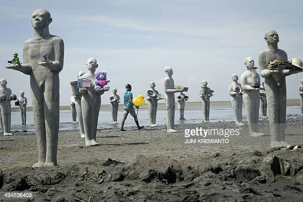 In this photograph taken on May 29 an art installation by Indonesian artist Dada Christanto shows sculptures symbolizing victims of the mud volcano...
