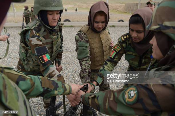 In this photograph taken on May 3 Afghan National Army female soldiers get their rifles at a range during a live firing exercise at the Kabul...