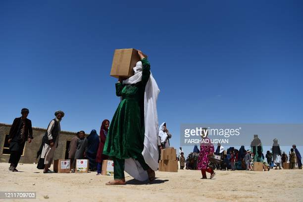 TOPSHOT In this photograph taken on May 3 an internally displaced woman carries free aid over her shoulders distributed during the Holy month of...