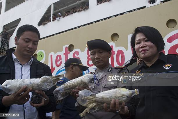 In this photograph taken on May 4 2015 Indonesian police and customs officials hold rare Indonesian yellowcrested cockatoos placed inside water...