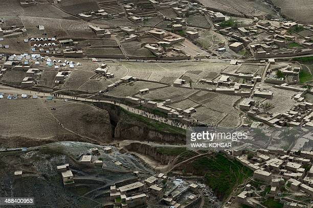 In this photograph taken on May 5, 2014 Afghan landslide-affected villagers gather near tents during aid distribution in Aab Bareek village at Argo...